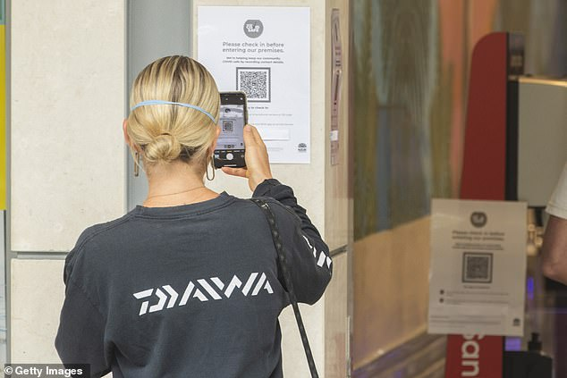 NSW is preparing to dump most of its contact tracing system in favour of an app that will alert residents when they've been exposed to the coronavirus (pictured, a Sydney shopper uses a QR code to check in to a shop, which will soon alert you to any exposure)