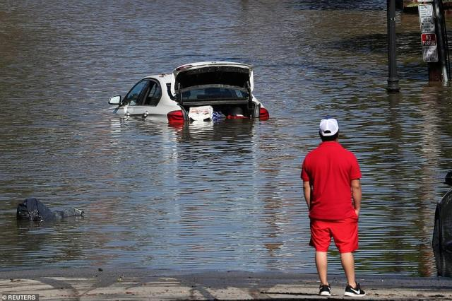 A man looks at a car in flood waters after remnants of Ida brought drenching rain, flash floods and tornadoes to parts of the Northeast in Mamaroneck, New York