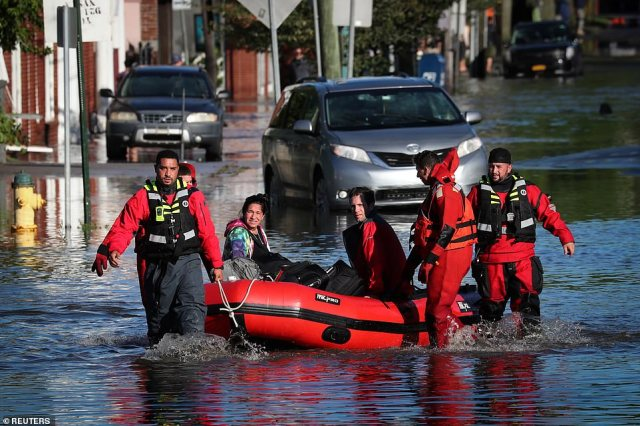 First responders pull local residents in a boat as they perform rescues of people trapped by floodwaters after the remnants of Tropical Storm Ida brought drenching rain, flash floods and tornadoes to parts of the northeast in Mamaroneck, New York,