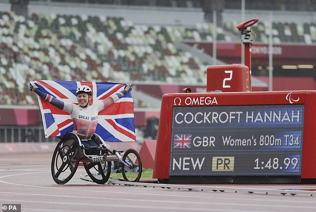 The British star holds the Union Jack flag aloft as she poses next to her time of 1:48.99