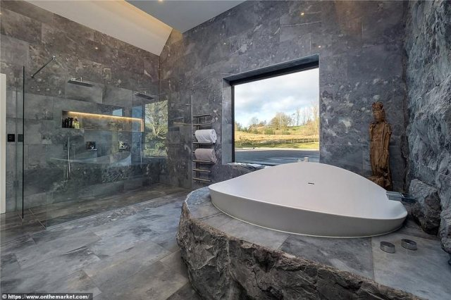 A large bath offers views of the countryside outside through a large window that allows light to stream into the bathroom
