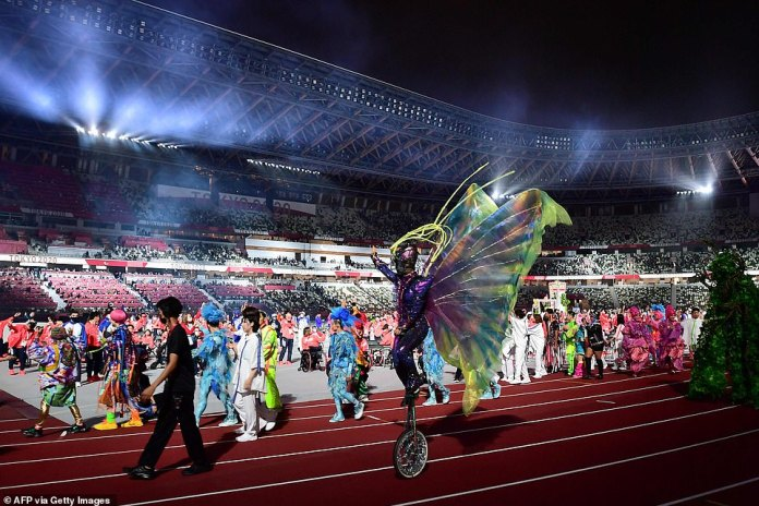 Performers wave at the end of the closing ceremony for the Tokyo 2020 Paralympic Games at the Olympic Stadium in Tokyo wearing bright clothes and displaying their best circus skills