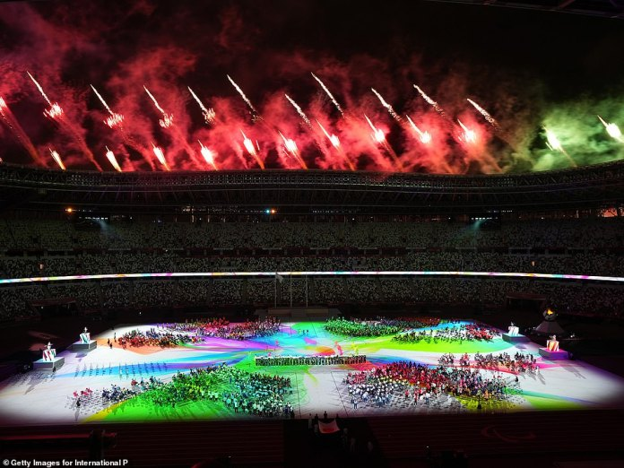 Fireworks light the sky red and projections on the floor of the stadium highlight the athletes and entertainers below