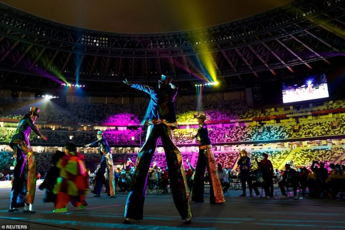 Stilt walkers showed off their skills as they marched around the track in the stadium wearing top haps and bright clothes