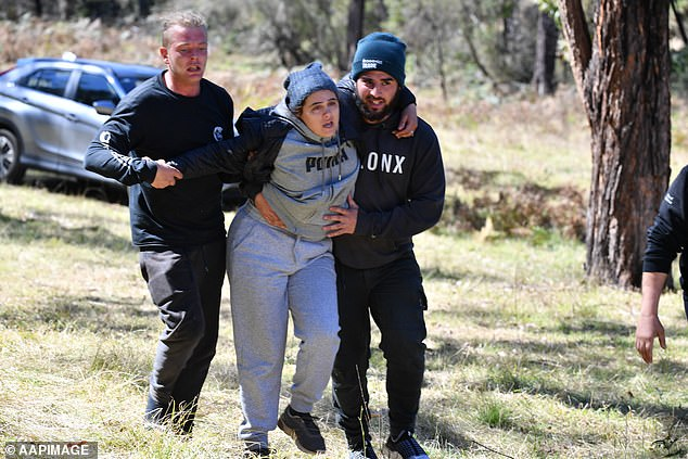 Kelly Elfalak (pictured) is helped from the ground by family members after being told her son had been found