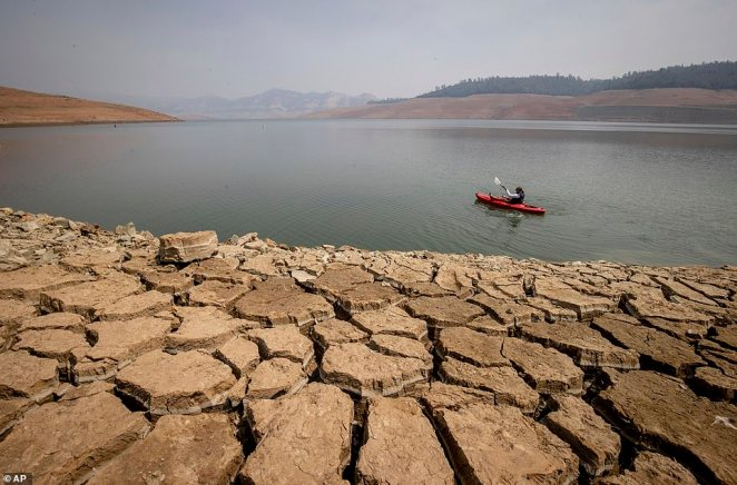 A kayaker paddles on the surface of Lake Oroville as water levels remain low due to continuing drought conditions in Oroville, Calif., Sunday, Aug. 22, 2021