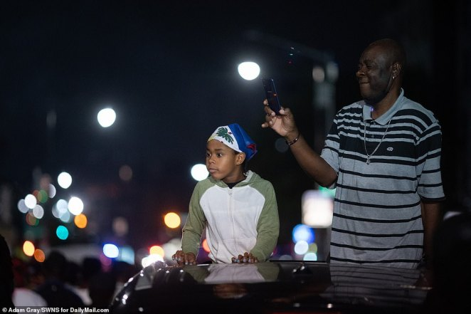 A man records the festivities on his cell phone as a young boy next to him looks on in Brooklyn on Monday