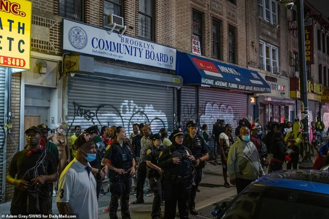 NYPD officers and onlookers watch as partygoers stage unofficial J'Ouvert festivities before dawn on Monday