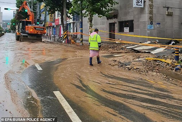 City workers clear up a muddy water underway on a road in Busan, South Korea on August 24