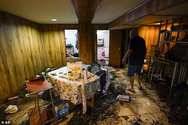 Felix Delapuente, a neighbor of the couple and child who drowned in their basement, shows the flood damage in his basement