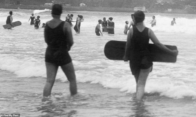 A very British holiday: Two women are seen walking into the sea at Newquay beach in Cornwall in 1925. One of them is carrying a rudimentary body board. In the background, children and their parents splash about in the water