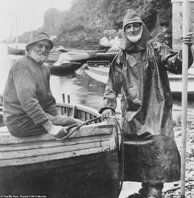 These two fishermen are seen in Looe, Cornwall, in 1903. One of the grizzled men is wearing a full-body rain coat, complete with hood. The man sitting next to him is sporting a jumper and cap