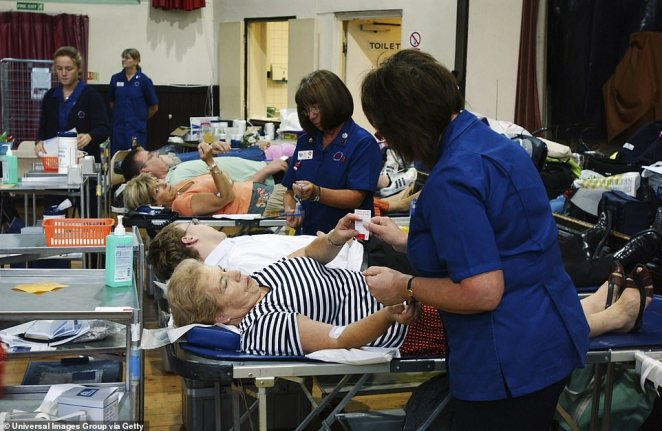 Nurses attend blood donors on beds during session at NHS National Blood Service collection centre
