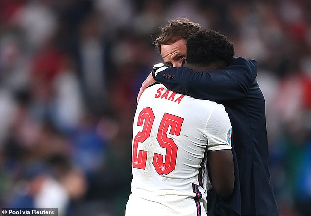Manager Gareth Southgate hugs Bukayo Saka after he missed his penalty, that sparked an torrent of foul online abuse now revealed to be mainly from racists abroad