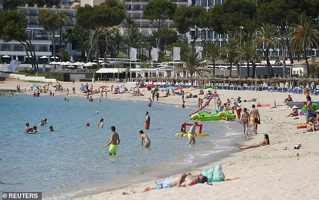 People enjoy themselves at Magaluf beach in Mallorca - a popular destination for UK holidaymakers - earlier this summer