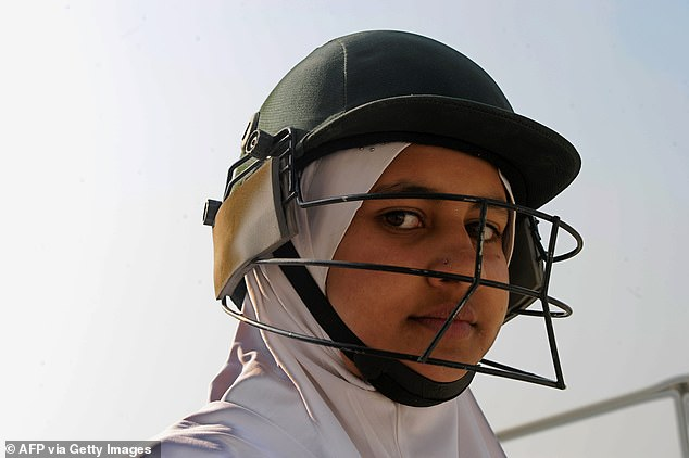 An Afghan girl watches during a cricket game on the school grounds in Kabul on December 28, 2010. Cricket has been popular with both genders since the Taliban were ousted by coalition forces but now women won't be allowed to play because the jihadists think it is immodest