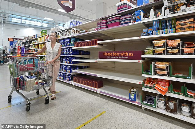 A sign advising products are temporarily out of stock is displayed in a supermarket in London