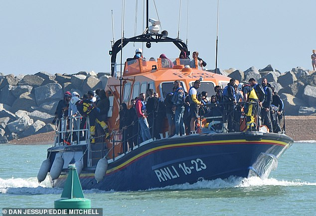 Dozens of migrants are brought ashore on an RNLI lifeboat in Eastbourne this afternoon