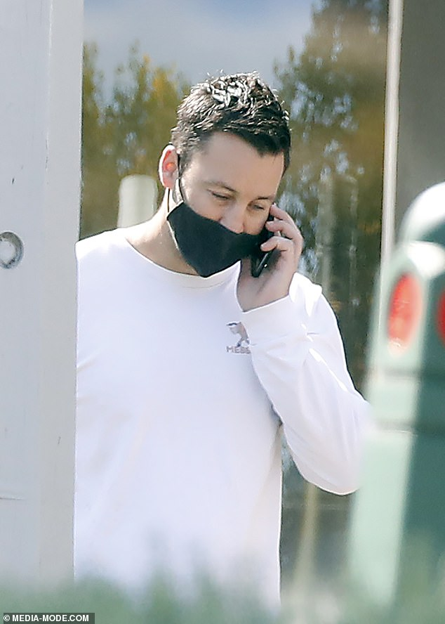Out and about:The footy commentator also donned a face mask and chatted on the phone
