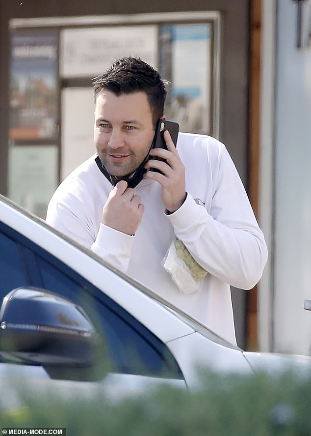 Catching up: A smiling Jimmy pulled down his face mask as he chatted to a friend driving past