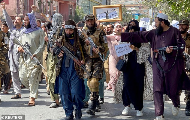 Taliban forces walk in front of Afghan demonstrators as they shout slogans during an anti-Pakistan protest on Tuesday