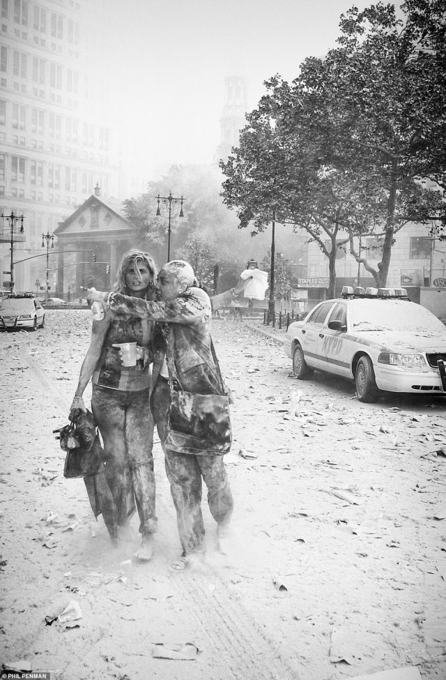 Joanne Capestro (on left with a coworker) is photographed by Phil Penman on 9/11 covered head to toe in thick dust and debris seconds after the South Tower fell as she fled from the World Trade Center