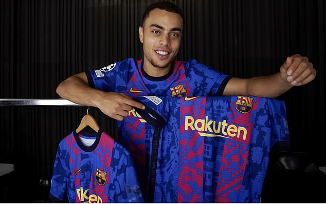 American full back Serginho Dest stands over a handful of shirts on display in a photoshoot