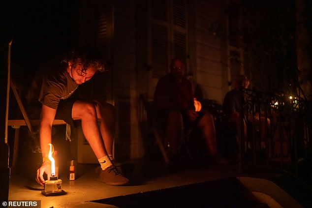 Jeremiah Lewis (pictured) adjusts a citronella candle on his neighbor's porch in the Bywater neighborhood, he is one of thousands of Louisiana residents left without power after Ida