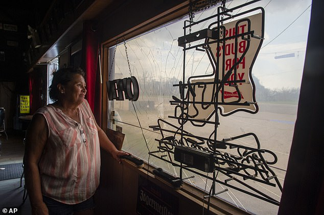 Debbie Malley, owner of Den Lounge in Venice, Louisiana stands near a cracked window as she cleans up her bar a week after Hurricane Ida
