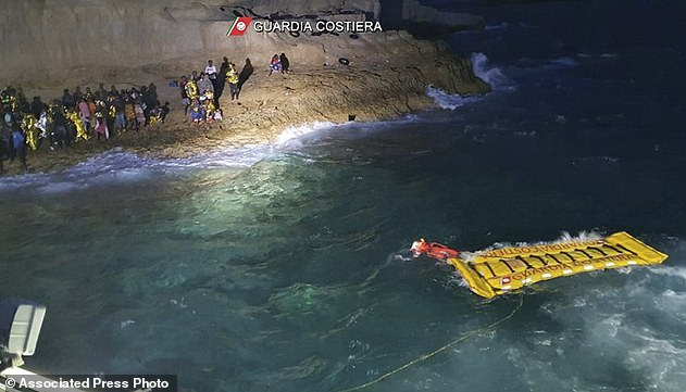 A coastguard officer swims the life raft over to the rocky shore as a pair of rescue boats wait nearby