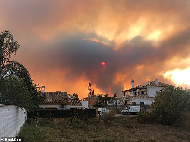 Smoke and orange light filled the sky over the Costa del Sol resort town of Estepona as wildfires forced an evacuation of the town on Thursday