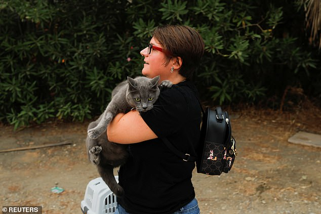 A woman carries her cat as officials evacuate people near the Costa del Sol resort of Estepona
