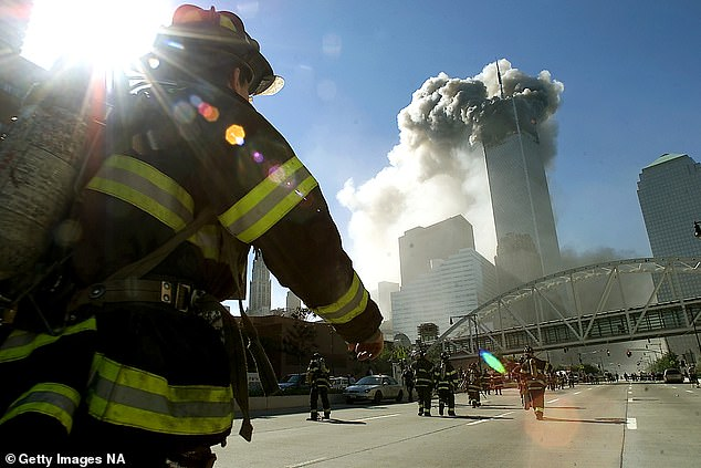 Researchers compared 10,786 firefighters who worked at the WTC site to 8,813 firefighters who didn't work at the site and found the WTC firefighters were 13% more likely of being diagnosed with cancer than their colleagues. Pictured: Firefighters walk towards one of the tower at the World Trade Center before it collapsed on 9/11