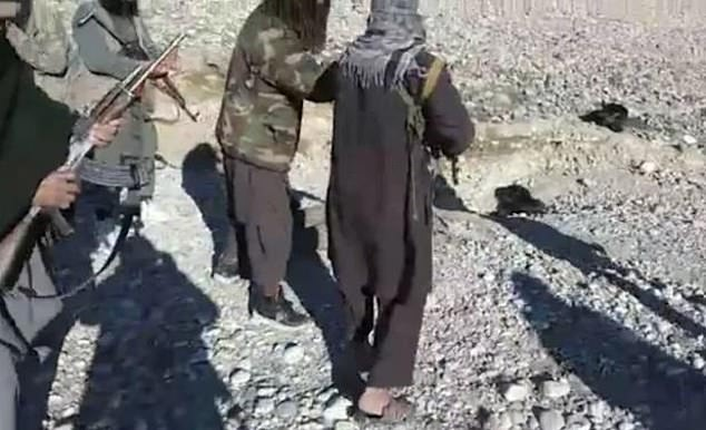 The Taliban shared a sickening video of six fighters chanting around the body of an Afghan solider as they carried his head by the hair. Pictured: A still from the harrowing clip of Taliban fighters