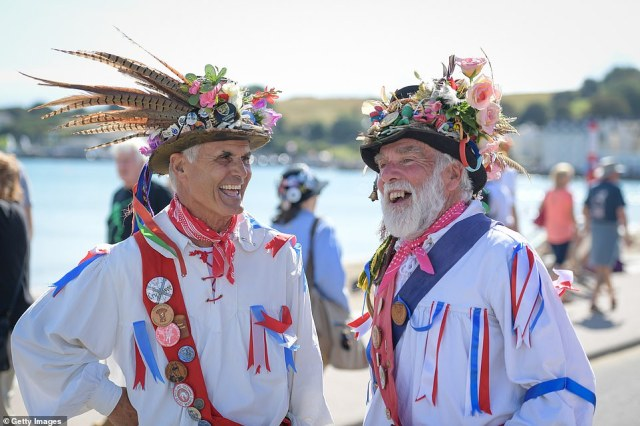 Tomorrow will be slightly cooler at 72F (22C), although still around average or above average for this time of year, before rainier spells later in the week. Pictured: Eynsham Morris dancers laugh during the dry weather in Swanage, England, today