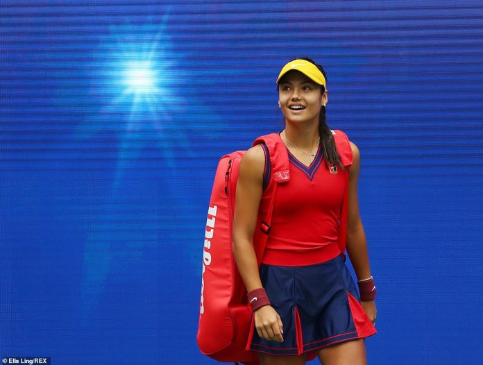 Raducanu looks up to the stands as she walks out with her bag over her shoulders for the final