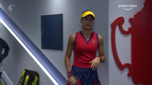 Raducanu, wearing a red and blue ensemble made by Nike, in the tunnel before heading out