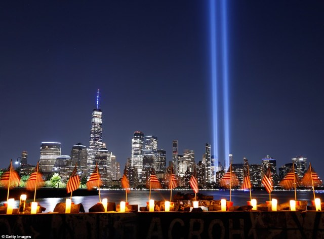 The Tribute in Light is illuminated above lower Manhattan and One World Trade Center in New York City behind a row of candles and flags on the 20th anniversary of the 9/11 attacks