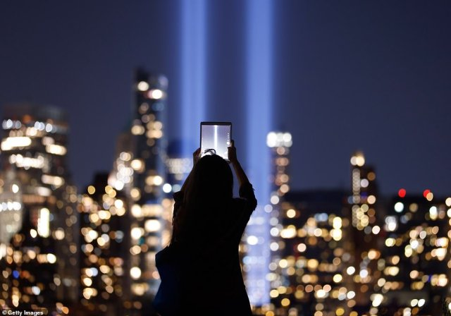 : A woman photographs the Tribute in Light as it is illuminated above lower Manhattan in New York City on the 20th anniversary of the 9/11 attacks as seen from Jersey City, New Jersey