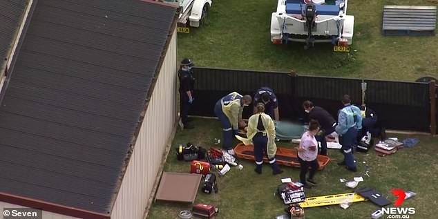 The woman's daughter and a neighbour rushed to help but the dog then turned on them, savaging the second woman, ripping her flesh from the bone, and snapping at the man trying to save them (pictured, medics work on the victims at the scene)
