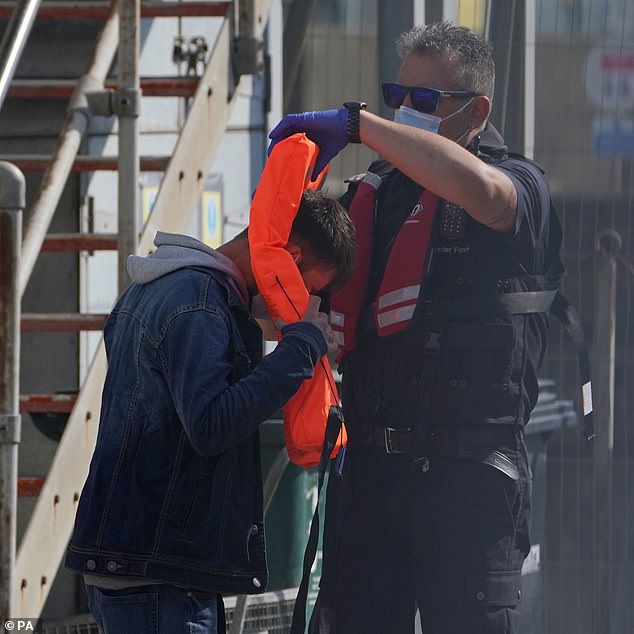 The body of a man has been recovered by the coastguard in the English Channel, Sussex Police have said. Pictured: A Border Force official helps a migrant remove his life jacket