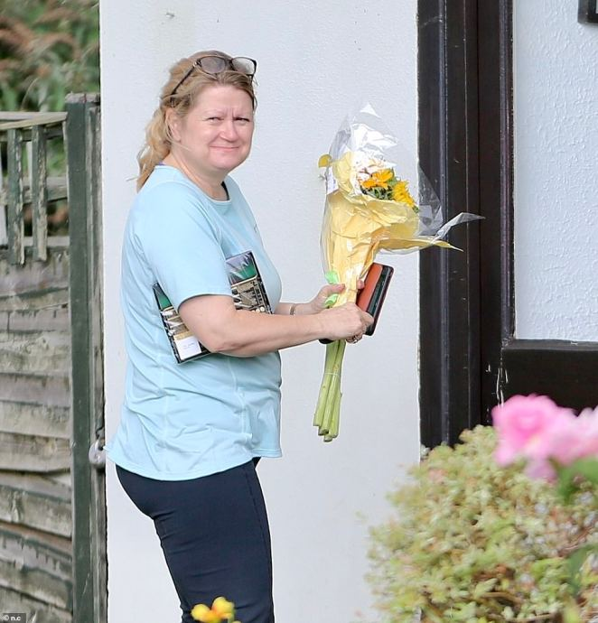 The home of tennis player Emma Raducanu in south London where the friends and locals have put banners outside their homes to celebrate her win at the US open. Above: A woman leaves a small bouquet of flowers on the doorstep