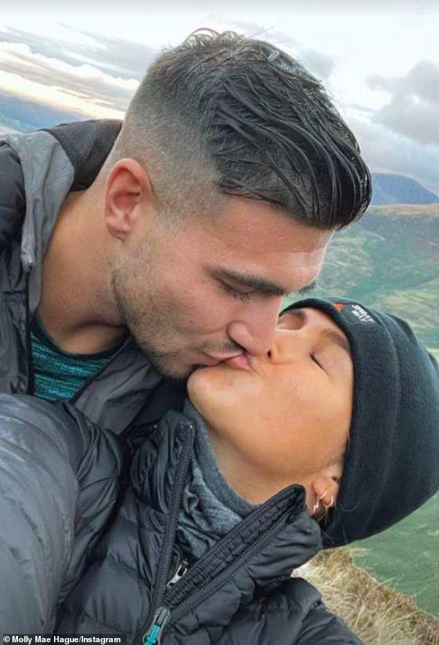 Cute: The couple looked loved-up pair shared a quick smooch in their walking gear with beautiful hilly scenery in the background