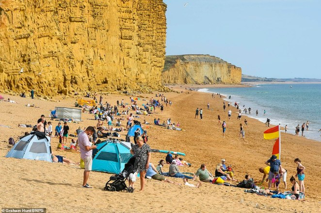 After last week's 86F, fresh heat arrives from the subtropics on Tuesday - as shown on a weather map - sucked north by powerful Larry, now nearing Iceland (pictured: West Bay, Dorset today)