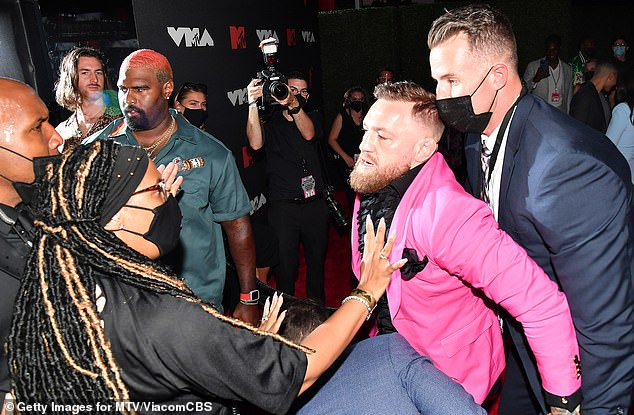 Escalating: Kelly's lady Megan Fox stepped in between the two men and eventually security pulled the professional fighter back away from the rocker