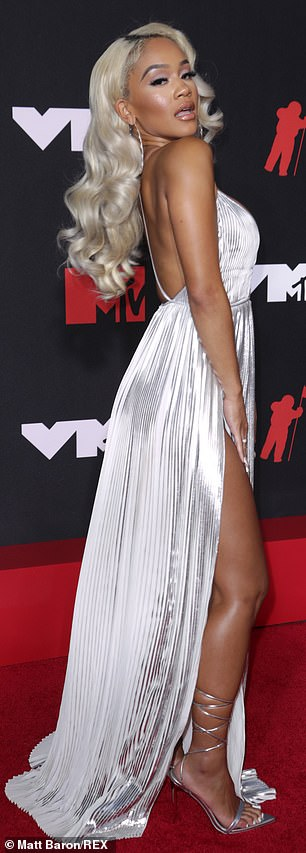 Silver belle: The half-Black, half-Filipina stunner teamed the slinky dress with a pair of matching stilettos which featured a strap which wrapped up her leg to just under the calf