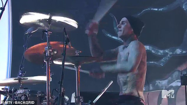 Rocking out:Travis was positioned behind him on stage but faced off to the side. He was shirtless as usual to show off his abundant tattoos