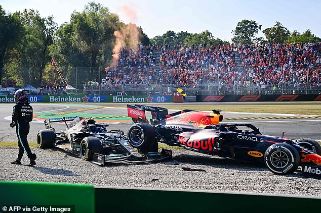 Hamilton (left) walks away from the scene of the crash as stunned spectators watch on