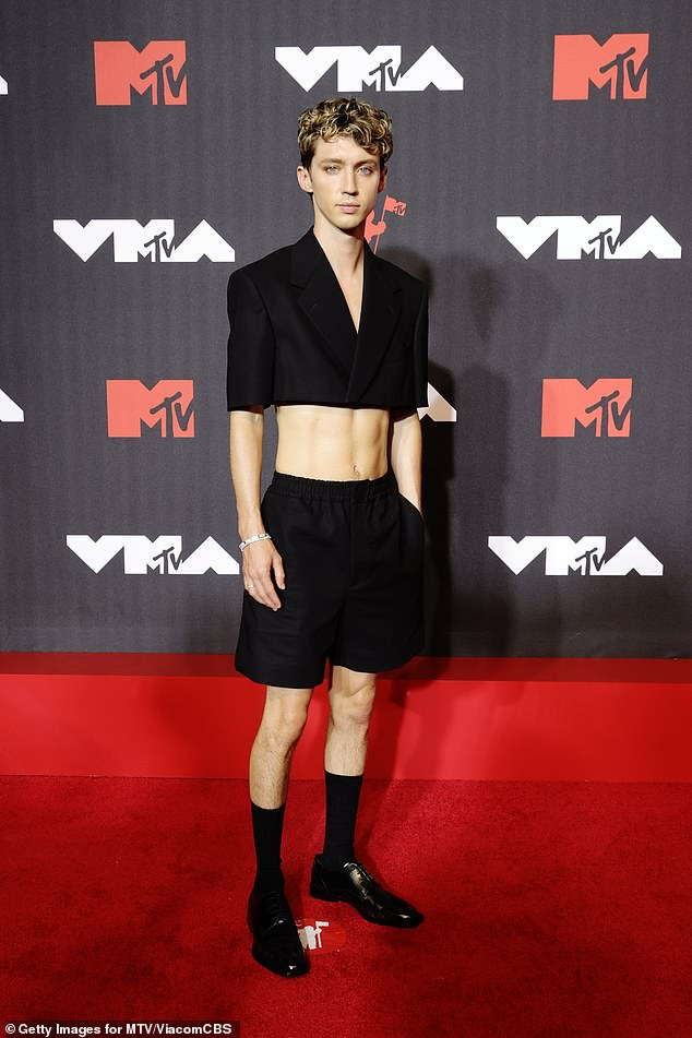 Unique style:Troye teamed the ensemble with black shorts, matching coloured high socks and a pair of shoes