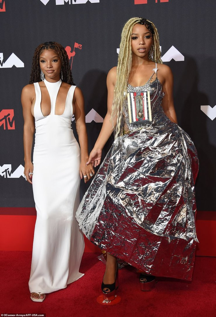 Stunning sisters: Halle Bailey was radiant in a white silk Monot while her sister Chloe went with a space-age silver look from Marni